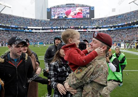 Salute to Service, Eric Roth, Rowan Roth. Spc. Eric Roth, right, hugs his son, Rowan, center, after surprising his family with his homecoming during a timeout in the first half of an NFL football game between the Carolina Panthers and the Atlanta Falcons in Charlotte, N.C