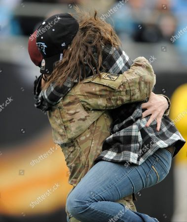 Eric Roth, Danielle Roth. Spc. Eric Roth, left, hugs his wife, Danielle, right, after surprising her with his homecoming during a timeout in the first half of an NFL football game between the Carolina Panthers and the Atlanta Falcons in Charlotte, N.C