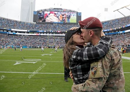 Salute to Service, Eric Roth, Danielle Roth. Spc. Eric Roth, right, kisses and hugs his wife, Danielle, left, after surprising her with his homecoming during a timeout in the first half of an NFL football game between the Carolina Panthers and the Atlanta Falcons in Charlotte, N.C