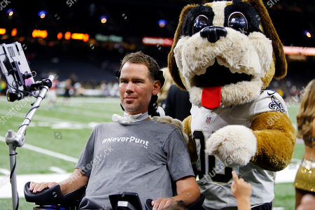 """Former New Orleans Saints Steve Gleason is escorted by the Saints mascot """"Gumbo"""" before an NFL football game against the Atlanta Falcons in New Orleans"""