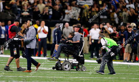 Former New Orleans Saints player Steve Gleason rides onto the field with with his son Rivers before an NFL football game against the Atlanta Falcons in New Orleans