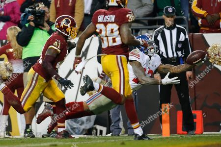 New York Giants wide receiver Odell Beckham (13) dives into the end zone for a touchdown as Washington Redskins cornerback Will Blackmon (41) and free safety Dashon Goldson (38) chase him during the second half of an NFL football game in Landover, Md