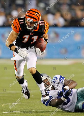Cincinnati Bengals' Jordan Shipley (11) slips the tackle of Dallas Cowboys' Jamar Wall on a 63-yard punt return in the fourth quarter of the Hall of Fame NFL football game, in Canton, Ohio. The Cowboys won 16-7