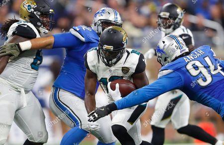 Denard Robinson, Haloti Ngata, Ezekiel Ansah. Jacksonville Jaguars running back Denard Robinson (16) rushes between the defense of Detroit Lions defensive tackle Haloti Ngata, left, and defensive end Ezekiel Ansah (94) during the second half of an NFL football game, in Detroit
