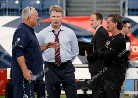 Television announcer and former NFL quarterback Phil Simms, second from left, talks with people on the field before an NFL football game, in Nashville, Tenn
