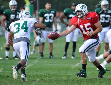 Tim Tebow, John Griffin. New York Jets quarterback Tim Tebow hands the ball off to running back John Griffin (34) at their NFL football training camp, in Cortland, N.Y