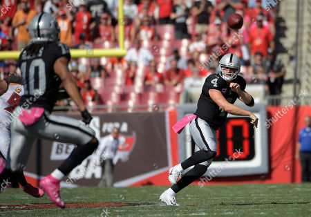 Oakland Raiders quarterback Derek Carr (4) looks for wide receiver Seth Roberts (10) during the third quarter of an NFL football game, in Tampa, Fla