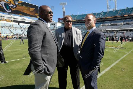 Jacksonville Jaguars general manager David Caldwell, right, chats with Oakland Raiders general manager Reggie McKenzie, center, and Joey Clinkscales, Raiders director of player personnel, before an NFL football game in Jacksonville, Fla