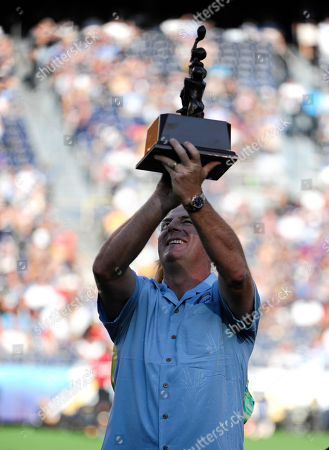 Former San Diego Chargers Darren Bennett holds up a trophy after be inducted into the Charger Hall of Frame during half time of an NFL football game against the Baltimore Ravens, in San Diego