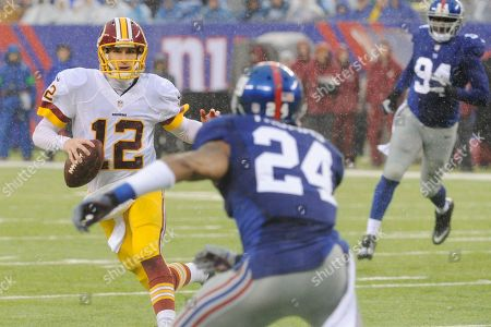 Washington Redskins' Kirk Cousins (12) avoids New York Giants' Terrell Thomas (24) during the first half of an NFL football game, in East Rutherford, N.J