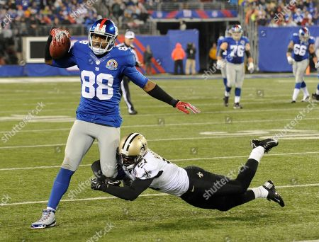 New York Giants wide receiver Hakeem Nicks (88) is tackled by New Orleans Saints outside linebacker Jonathan Vilma (51) during the second half of an NFL football game, in East Rutherford, N.J