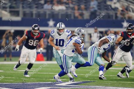 Dustin Vaughan, Gus Johnson. Dallas Cowboys quarterback Dustin Vaughan (10) hands the ball to running back Gus Johnson (37) during the first half of a preseason NFL football game, in Arlington, Texas
