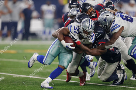 Gus Johnson, Justin Tuggle. Dallas Cowboys running back Gus Johnson (37) is tackled by Houston Texans inside linebacker Justin Tuggle, rear, and host of players during the first half of a preseason NFL football game, in Arlington, Texas