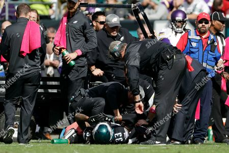 Team personnel check on Philadelphia Eagles' Ron Brooks (33) as he lies injured on the field during the first half of an NFL football game against the Minnesota Vikings, in Philadelphia