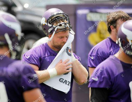 Minnesota Vikings guard Joe Berger (61) wipes his face during an NFL mini camp in Eden Prairie, Minn