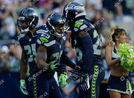Seattle Seahawks defensive players (from left) DeShawn Shead, Earl Thomas, and Richard Sherman, greet each other during a preseason NFL football game against the Minnesota Vikings, in Seattle