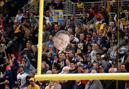 Fans hold up a picture of Dave Peacock during the third quarter of an NFL football game between the St. Louis Rams and the Tampa Bay Buccaneers, in St. Louis. Peacock is heading up a group trying to build a new downtown stadium in an effort to keep the Rams in St. Louis