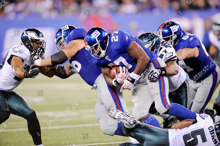 Stock Image of Cullen Jenkins, Brandon Jacobs, David Baas. Philadelphia Eagles defensive tackle Cullen Jenkins (97) beats New York Giants David Baas (64) to tackle Brandon Jacobs (27) during the third quarter of an NFL football game in East Rutherford, N.J