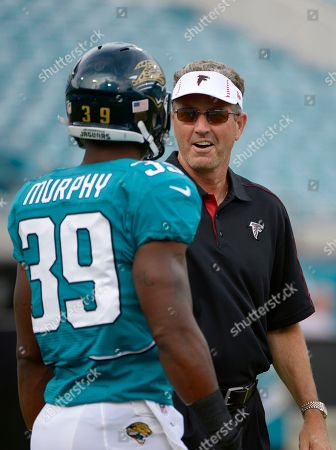 Dirk Koetter, Richard Murphy. Atlanta Falcons offensive coordinator Dirk Koetter, right, talks with Jacksonville Jaguars running back Richard Murphy (39) during warmups prior to a preseason NFL football game in Jacksonville, Fla