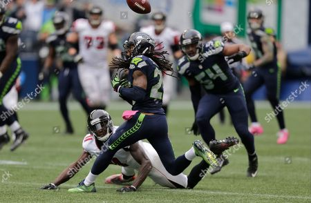Richard Sherman, Julio Jones. Seattle Seahawks cornerback Richard Sherman (25), center, reaches for a pass intended for Atlanta Falcons wide receiver Julio Jones, lower left, in the second half of an NFL football game, in Seattle. The pass was intercepted by Seahawks' Earl Thomas and the Seahawks beat the Falcons 26-24
