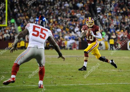 Stock Image of Robert Griffin III, Keith Rivers. Washington Redskins quarterback Robert Griffin III (10) scrambles as New York Giants outside linebacker Keith Rivers (55) pursues him, during the second half of an NFL football game, in Landover, Md