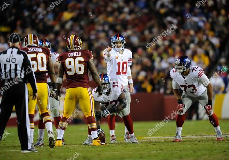 New York Giants quarterback Eli Manning (10) points against Washington Redskins outside linebacker Rob Jackson (50) and Barry Cofield (96) during the first half of an NFL football game, in Landover, Md. Also seen is New York Giants guard James Brewer (73