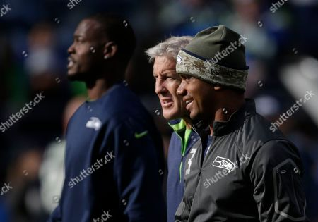 Seattle Seahawks head coach Pete Carroll, center, walks with quarterback Russell Wilson, right, and backup quarterback Tarvaris Jackson, left, before an NFL football game between the Seattle Seahawks and the New York Giants, in Seattle