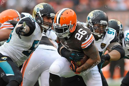 Willis McGahee, Jason Babin, Roy Miller. Cleveland Browns running back Willis McGahee (26) runs with the ball against Jacksonville Jaguars defensive end Jason Babin, left, and defensive tackle Roy Miller (97) during an NFL football game, in Cleveland. Jacksonville won 32-28