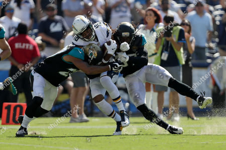 San Diego Chargers wide receiver Tyrell Williams is hit by Jacksonville Jaguars cornerback Dwayne Gratz, left, and strong safety Johnathan Cyprien, right, on his way to scoring a touchdown during the second half of an NFL football game, in San Diego