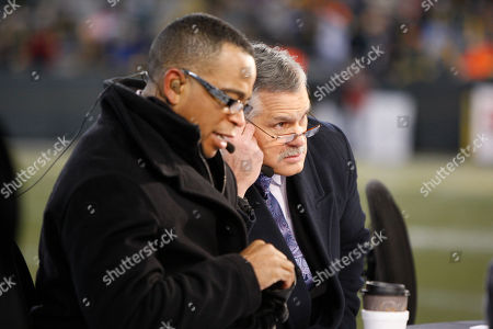 ESPN announcer Matt Millen, right, and Stuart Scott are seen before the first half of an NFL football game between the Green Bay Packers and Baltimore Ravens, in Green Bay, Wis