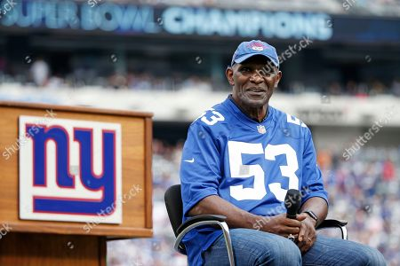 Former New York Giants player Harry Carson listens during a halftime ceremony of an NFL football game between the New York Giants and the New Orleans Saints, in East Rutherford, N.J