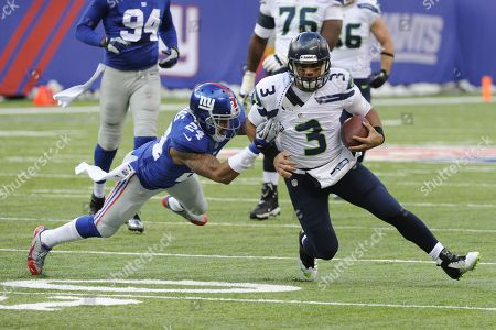 Russell Wilson, Terrell Thomas. Seattle Seahawks quarterback Russell Wilson (3) runs with the ball as New York Giants cornerback Terrell Thomas (24) tries to tackle him during the first half of an NFL football game, in East Rutherford, N.J