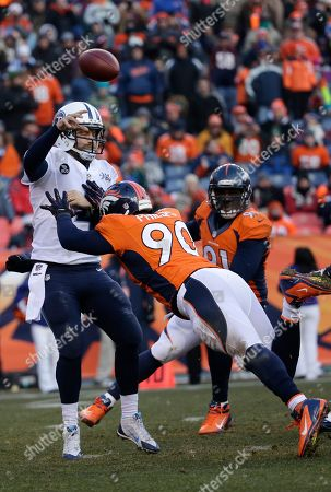 Tennessee Titans quarterback Ryan Fitzpatrick (4) is pressured by Denver Broncos defensive end Shaun Phillips (90) during the first half of an NFL football game, in Denver