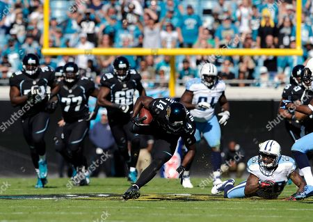 Justin Blackmon, Jordan Babineaux. Jacksonville Jaguars wide receiver Justin Blackmon (14) tries to keep his balance after being tripped up by Tennessee Titans strong safety Jordan Babineaux (26) during the first half of an NFL football game, in Jacksonville, Fla