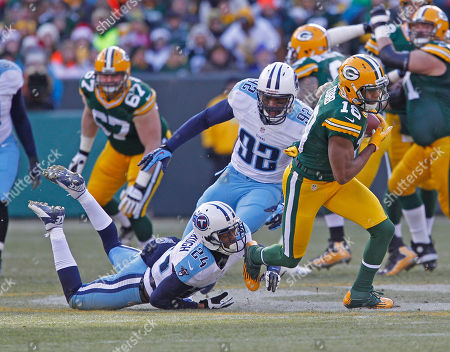Stock Photo of Randall Cobb, Coty Sensabaugh, Jordan Babineaux. Green Bay Packers wide receiver Randall Cobb breaks the tackle of Tennessee Titans cornerback Coty Sensabaugh during an NFL football game, in Green Bay, Wis