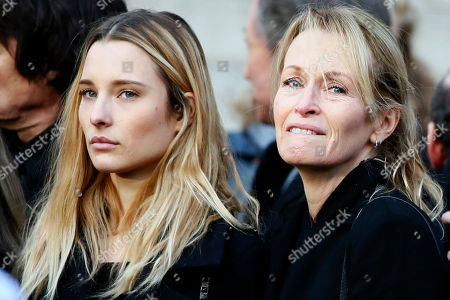 Estelle Lefebure, right, and her daughter Ilona Smet leave after the funeral ceremony in tribute to late French rock star Johnny Hallyday, in Paris, Saturday, Dec.9, 2017. France is bidding farewell to its biggest rock star, honoring Johnny Hallyday with an exceptional funeral procession down the Champs-Elysees, a presidential speech and a motorcycle parade, all under intense security