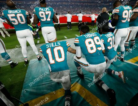Kenny Stills, Julius Thomas, Michael Thomas. Miami Dolphins wide receiver Kenny Stills (10), tight end Julius Thomas (89) and strong safety Michael Thomas (31), kneel during the National Anthem, before the first half of an NFL football game against the New England Patriots, in Miami Gardens, Fla