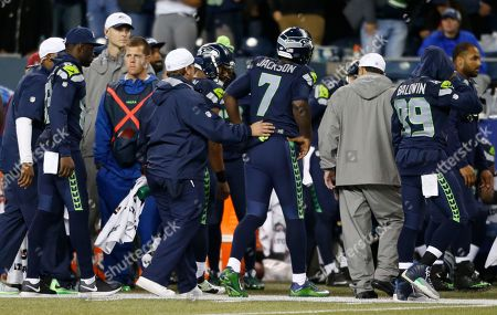 Seattle Seahawks quarterback Tarvaris Jackson (7) is helped off the field after he went down with an injury in the second half of a preseason NFL football game, in Seattle