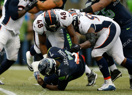 Denver Broncos linebacker Shaquil Barrett, left, and defensive end Antonio Smith, right, tackle Seattle Seahawks quarterback Tarvaris Jackson after Jackson got a pass off in the first half of a preseason NFL football game, in Seattle