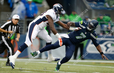 Denver Broncos linebacker Shaquil Barrett, left, pressures Seattle Seahawks quarterback Tarvaris Jackson in the first half of a preseason NFL football game, in Seattle