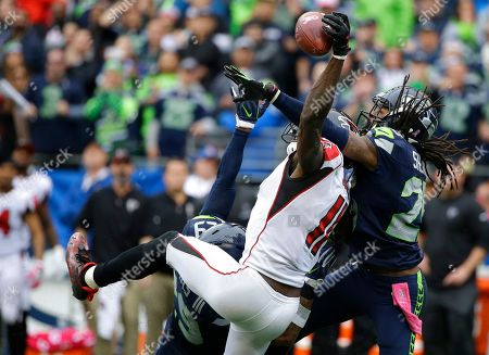 Richard Sherman, Julio Jones. Seattle Seahawks cornerback Richard Sherman, right, and Earl Thomas (obscured) break up a pass intended for Atlanta Falcons wide receiver Julio Jones (11) in the second half of an NFL football game, in Seattle. The Seahawks beat the Falcons 26-24