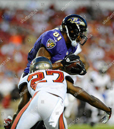 Stock Photo of Baltimore Ravens tight end Visanthe Shiancoe (81) is hit by Tampa Bay Buccaneers cornerback Johnthan Banks (27) during the first half of an NFL preseason football game, in Tampa, Fla
