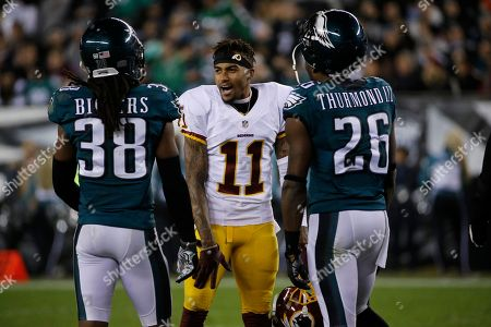 Washington Redskins' DeSean Jackson (11) meets with Philadelphia Eagles' E.J. Biggers (38) and Walter Thurmond (26) in the first half of an NFL football game, in Philadelphia