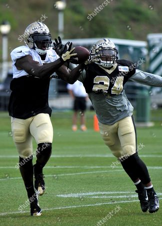 New Orleans Saints wide receiver Joseph Morgan (13) catches the ball with New Orleans Saints defensive back Kyle Wilson (24) reaching in for the interception, during the teams NFL football training camp in White Sulphur Springs, W. Va