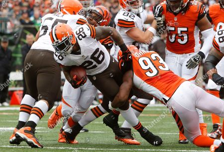 Willis McGahee, Michael Johnson. Cleveland Browns running back Willis McGahee (26) is tackled by Cincinnati Bengals defensive end Michael Johnson (93) in the first half of an NFL football game, in Cincinnati