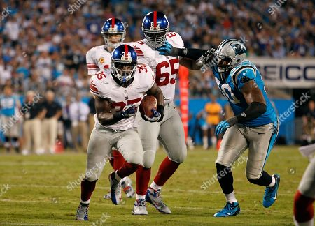 Andre Brown, Frank Alexander, Will Beatty. New York Giants' Andre Brown (35) starts his run as Carolina Panthers' Frank Alexander (90) pushes away from New York Giants' Will Beatty (65) during the first half of an NFL football game in Charlotte, N.C., . The Giants won 36-7