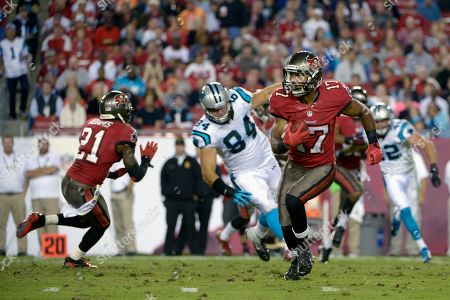 Stock Photo of Eric Page, Michael Adams, Ben Hartsock. Tampa Bay Buccaneers wide receiver Eric Page (17) returns a kickoff as defensive back Michael Adams (21) blocks Carolina Panthers' Ben Hartsock (84) during the second half of an NFL football game in Tampa, Fla