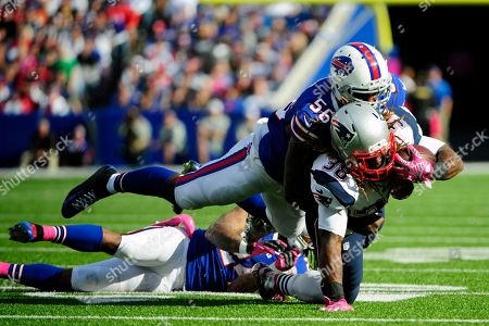Stock Photo of Buffalo Bills outside linebacker Keith Rivers (56) tackles New England Patriots' Brandon Bolden (38) during the second half of an NFL football game, in Orchard Park, N.Y