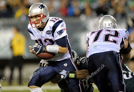 New England Patriots quarterback Tom Brady (12) hangs onto the ball during the first half of an NFL football game with the Philadelphia Eagles in Philadelphia