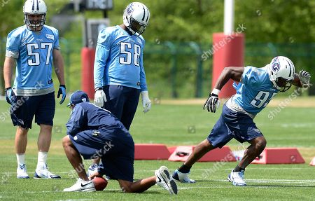 Patrick Bailey, Shaun Phillips, Kamerion Wimbley. Tennessee Titans linebackers Patrick Bailey (57), Shaun Phillips (58), and Kamerion Wimbley (95) run drills during an NFL football minicamp workout, in Nashville, Tenn